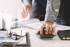 Businessman hand working with finances about cost and calculator. And latop with mobile phone on withe desk in modern office with VR icon diagram Stock Images