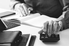 Businessman hand working with finances about cost and calculator. And latop with mobile phone on withe desk in modern office ,black and white Stock Photos