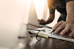 Businessman hand working with new modern computer and business. Strategy documents layers with glass of water and eye glasses foreground on wooden desk in Royalty Free Stock Image
