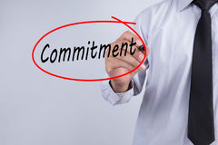 Businessman Hand Writing commitment with a marker over transpare Stock Photo