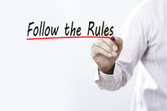 Businessman hand writing Follow the Rules with red marker on transparent wipe board, business concept stock photo