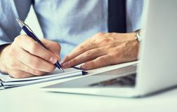 Businessman hand writing note on a notebook. Business man working at office desk. Close up of empty notebook on a. Businessman hand writing note on a notebook royalty free stock photography