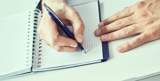 Businessman hand writing note on a notebook. Business man working at office desk. Close up of empty notebook on a. Businessman hand writing note on a notebook royalty free stock photos