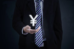 Businessman hand with yen currency sign. Picture of a businessman hand holding a yen currency sign while wearing formal suit Stock Photos