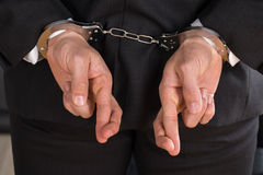 Businessman With Handcuffs. Close-up Of Businessman With Handcuffs And Finger Crossed. Crossed Fingers As A Symbol Of Breach Of Contract Stock Photos