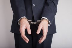 Businessman in handcuffs on gray background stock images
