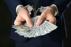 Businessman in handcuffs holding bribe,. Closeup Stock Photography