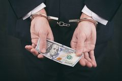 Businessman in handcuffs holding bribe hundred dollars stock photo