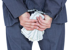 businessman in handcuffs holding bribe Royalty Free Stock Photography