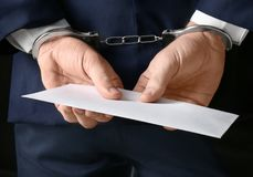 Businessman in handcuffs holding envelope with bribe, stock photos
