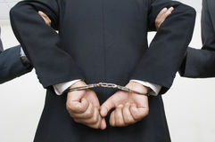 Businessman With Handcuffs While Partners Holding His Arms Royalty Free Stock Images