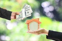 Businessman handed the money to Businesswoman holding wooden house on white background, Real estate trading and loan concepts royalty free stock photo