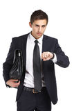 Businessman handing bag and looking at his watch Royalty Free Stock Photo