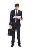 Businessman handing briefcase and reading docs Stock Images