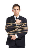 Businessman handing briefcase tied with the string. Portrait of businessman handing briefcase who tied with the rope, isolated on white. Concept of slavery and Royalty Free Stock Photo