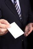 Businessman handing a businesscard. Businessman handing a blank businesscard - Focus on hand and card Stock Image