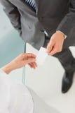 Businessman handing businesswoman his card Stock Photos