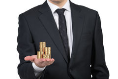 Businessman handing gold coins Stock Photo