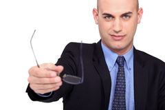 Businessman handing his glasses. Royalty Free Stock Images
