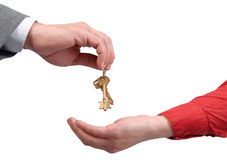 Businessman handing a key to a woman hand. Businessman handing a key to success over a woman palm Stock Photo