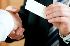 Businessman handing over business card royalty free stock image