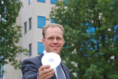 Businessman handing over a CD to viewer Stock Photography