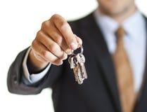 Businessman handing over keys Stock Image