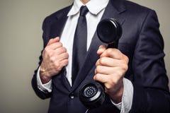 Businessman handing over a telephone Stock Photo