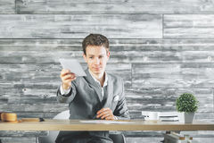 Businessman handing paper sheet. While sitting at office desk with coffee cup, supplies and decorative plant Royalty Free Stock Photos