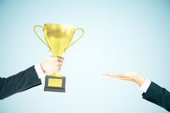 Businessman handing trophy blue background. Businessman handing golden cup trophy to another man on blue background. Mock up, 3D Rendering Stock Photography
