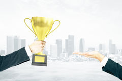 Businessman handing trophy city background Royalty Free Stock Images