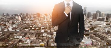 Businessman handles necktie showing confidence in the big city. Businessman handles necktie showing confidence Stock Photography