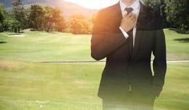 Businessman handles necktie showing confidence in golf course. Businessman handles necktie showing confidence in golf stock photo