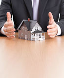 Businessman hands around house architectural model Royalty Free Stock Image