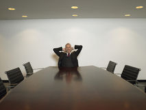 Businessman With Hands Behind Head In Conference Room Royalty Free Stock Photos