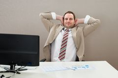 Businessman with hands behind head in office Royalty Free Stock Image