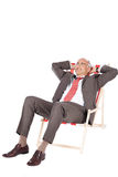 Businessman With Hands Behind Head Relaxing On Deck Chair Stock Photo