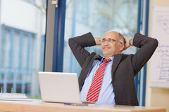Businessman With Hands Behind Head Sitting At Desk Royalty Free Stock Photo