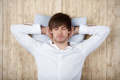Businessman With Hands Behind Head Sleeping On Wooden Wall Royalty Free Stock Images