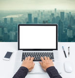 Businessman hands on blank screen laptop computer. With cityscape background Royalty Free Stock Images