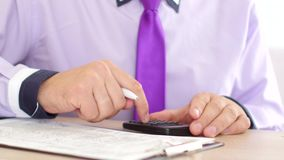Businessman hands with calculator and pen writing and filing papers or tax form. On table in his cabinet stock footage
