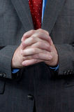 Businessman with hands clasped. A well dressed businessman in his business suit waits and hopes while standing with his hands clasped Royalty Free Stock Photo
