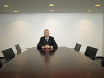 Businessman With Hands Clasped Sitting In Conference Room Stock Photos