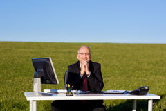 Businessman With Hands Clasped Sitting At Desk On Field Royalty Free Stock Photos