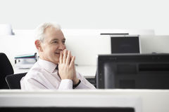 Businessman With Hands Clasped Sitting At Desk Royalty Free Stock Images