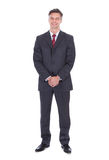 Businessman with hands clasped standing against white background. Full length portrait of smiling businessman with hands clasped standing against white Royalty Free Stock Photo