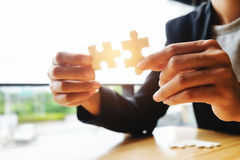Businessman hands connecting jigsaw puzzle. Business solutions, success and strategy, learning concept. Close up photo with small dof stock images