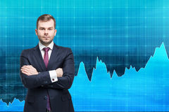 Businessman with hands crossed standing in front of a blue graph Royalty Free Stock Images