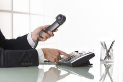 Businessman hands dialing out on a black deskphone Stock Photos