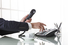 Businessman hands dialing out on a black deskphone Stock Images
